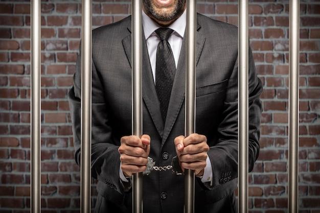 Деловой человек, держащий денежные купюры с наручниками в тюрьме. понятие коррупции, коррумпированных политиков, нелегального бизнеса. кирпичный фон.