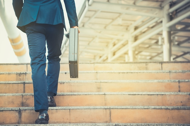 Business man holding a briefcase walking up the stairs in the routine of working with dete