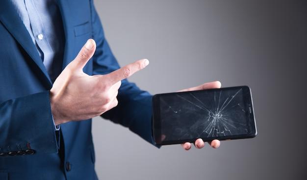 Business man holding broken screen tablet.