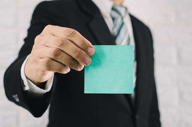 カード紙ポストイットノートを保持しているビジネスの男性