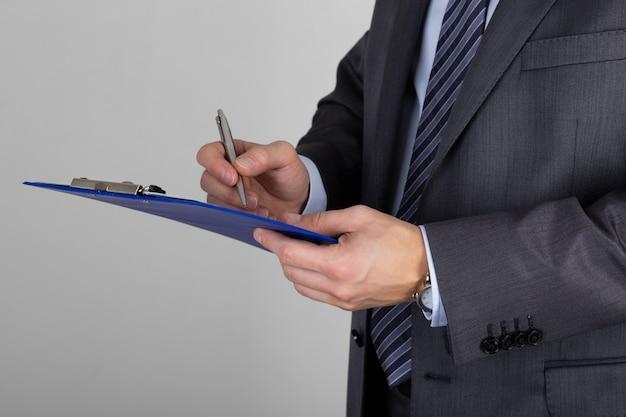 クリップボードを保持し、文書に署名するビジネスマン。契約またはパートナーシップ契約の購読
