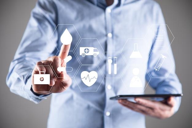 의료 아이콘으로 디지털 태블릿을 들고 사업가