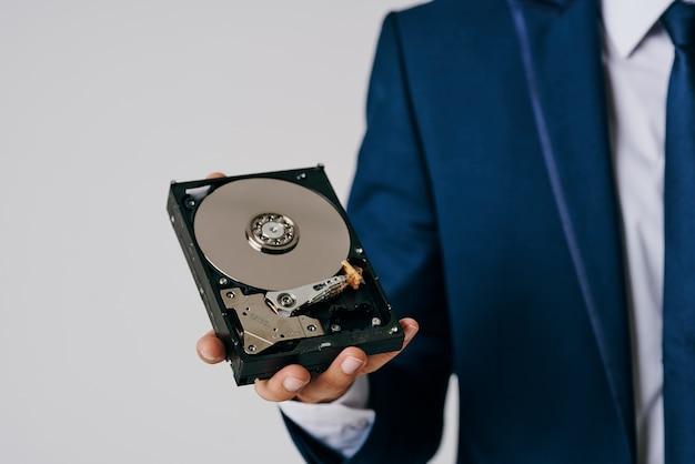 회색 공간에 분해 된 하드 드라이브를 들고 사업가