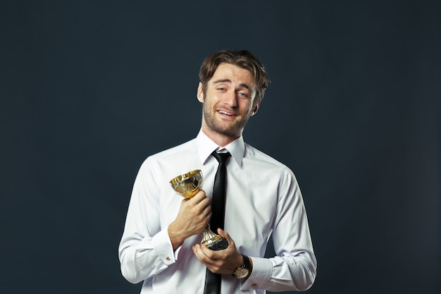 Business man holding golden cup trophy
