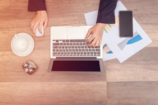 木製のテーブルに手をつないで、ペーパープリントのグラフデータでラップトップを入力するビジネスマン