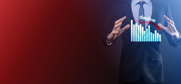 Деловой человек, держащий голографические графики и акции. наклон, уменьшение, вниз, падение. статистика бизнеса. карьера, деньги, концепция успеха. регрессия, кризис. концепция бизнеса и финансового кризиса