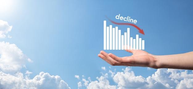 ホログラフィックグラフと株式を保持しているビジネスマン。減少、減少、下降、低下。ビジネス統計。キャリア、お金、成功のコンセプト。回帰、危機。ビジネスおよび金融危機の概念