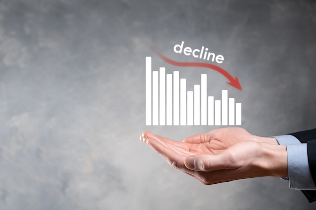 Деловой человек, держащий голографические графики и акции. снижение, уменьшение, снижение, падение.