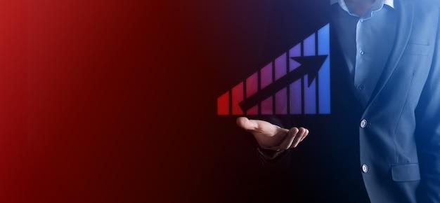 ホログラフィックグラフと株式市場の統計を保持しているビジネスマンは利益を得る。成長計画と事業戦略の概念。デジタル画面から経済性の高いディスプレイ。