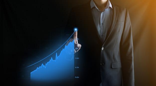 Деловой человек, держащий голографические графики и статистику фондового рынка, получает прибыль. концепция планирования роста и бизнес-стратегии. цифровой экран с хорошей экономичностью.