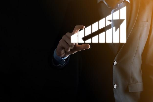 홀로그램 그래프와 주식 시장 통계를 들고 사업가 이익을 얻습니다. 성장 계획 및 비즈니스 전략의 개념. 경제성이 좋은 디지털 화면을 표시합니다.