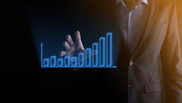 Деловой человек, держащий голографические графики и статистику фондового рынка, получает прибыль. концепция планирования роста и бизнес-стратегии. дисплей хорошей формы экономичного цифрового экрана.