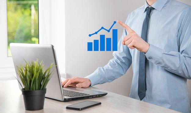 홀로그램 그래프와 주식 시장 통계를 들고 있는 사업가는 이익을 얻습니다. 성장 계획 및 비즈니스 전략의 개념입니다. 좋은 경제 형태의 디지털 화면의 표시.