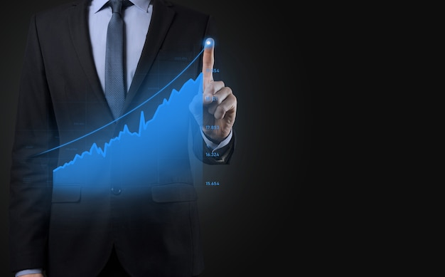 Business man holding holographic graphs and stock market statistics gain profits. concept of growth planning and business strategy. display of good economy form digital screen.