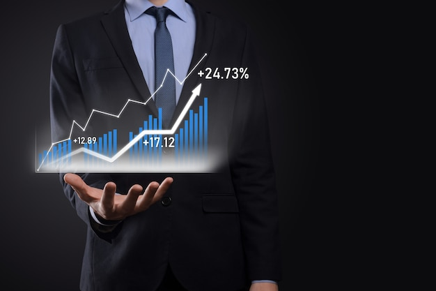 Business man holding holographic graphs and stock market statistics gain profits