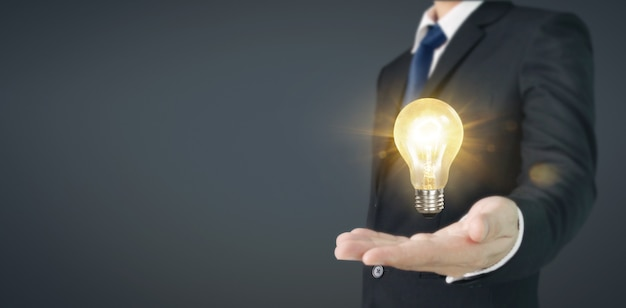 Business man holding illuminated light bulb