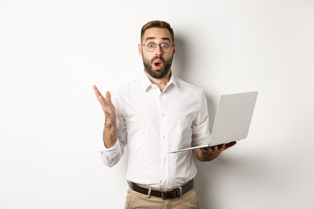 Бизнес. мужчина держит ноутбук и выглядит удивленным, удивленным веб-сайтом, стоя