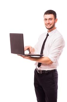 Uomo di affari che tiene un computer portatile - isolato sopra un muro bianco