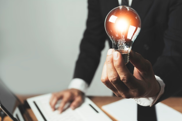 Business man holding a light bulb with coins money and copy space for accounting, ideas and creative concept.