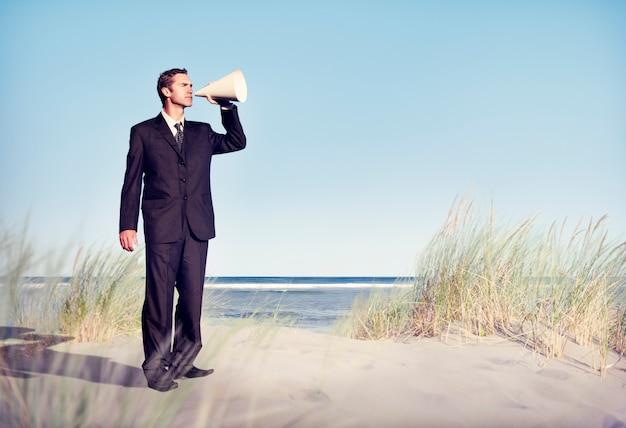Business man holding loudspeaker on beach