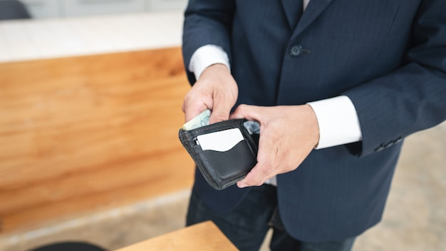 Business man holding men wallet while standing.