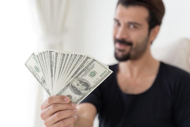 ホームオフィスでお金の米ドル札を保持しているビジネスマン