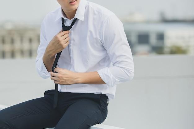 Business man holding necktie