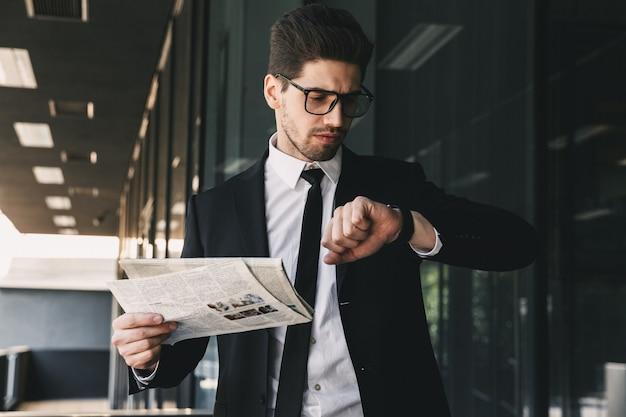 時計を見て新聞を保持しているビジネスマン。