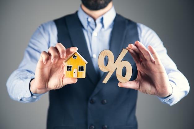 Деловой человек, держащий проценты с моделью дома