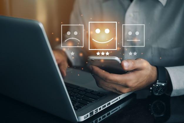 サービスに満足を与えるために幸せなスマイリーの顔のアイコンに仮想画面で電話を保持しているビジネスマン。評価は非常に感銘を受けました。カスタマーサービスと満足の概念