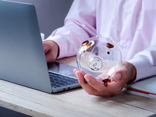 사무실에서 나무 테이블에 돼지 저금통을 들고 비즈니스 사람. 미래 계획 및 퇴직 기금, 비즈니스 또는 금융 저축 및 투자 비용을위한 저축