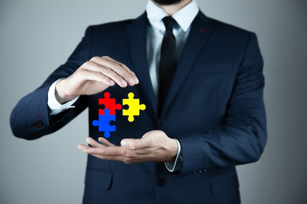Business man holding puzzle in screen