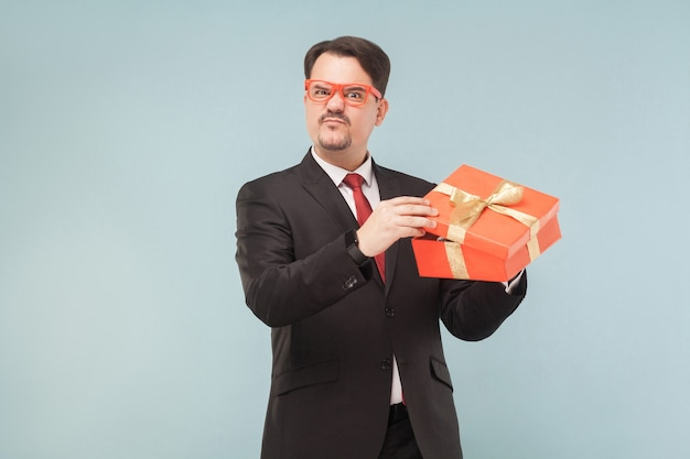 Business man holding red gift box disappointed with the gift