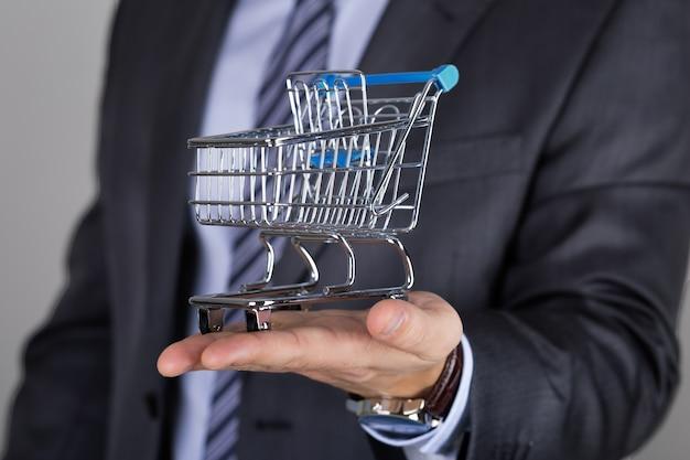 ショッピングカートを保持しているビジネスマン。ビジネスオファー、ショッピングまたは販売の概念