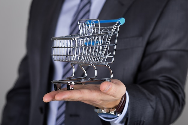 Business man holding shopping cart. business offer, shopping or sale concept