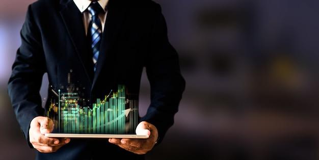 株式市場分析、ビジネスおよび取引市場の概念を備えた株式チャートと外国為替チャートのホログラフィックを備えたスマートデバイスを保持しているビジネスマン。