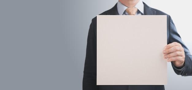 正方形のモックアップ紙を保持しているビジネスマン。スーツを着た男とバナーは、灰色の背景に紙の段ボールの空の正方形のシートを手に持っています。バナー。コピースペース