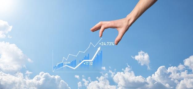 Деловой человек, держащий планшет и показывающий голографические графики и статистику фондового рынка, получает прибыль. концепция планирования роста и бизнес-стратегии. отображение хорошей формы экономичного цифрового экрана.