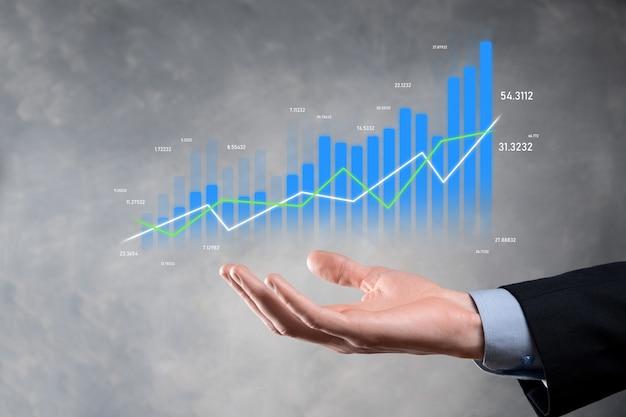 タブレットを持ってホログラフィックグラフと株式市場の統計を表示するビジネスマンは利益を得る。成長計画と事業戦略の概念。デジタル画面からの経済性の表示。