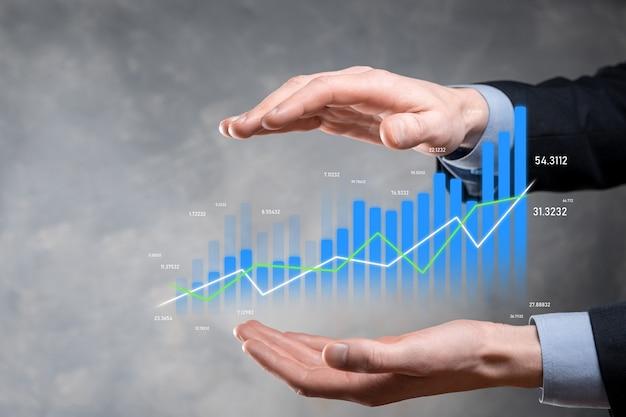Деловой человек, держащий планшет и показывающий голографические графики и статистику фондового рынка, получает прибыль. концепция планирования роста и бизнес-стратегии. дисплей хорошей формы экономичного цифрового экрана.