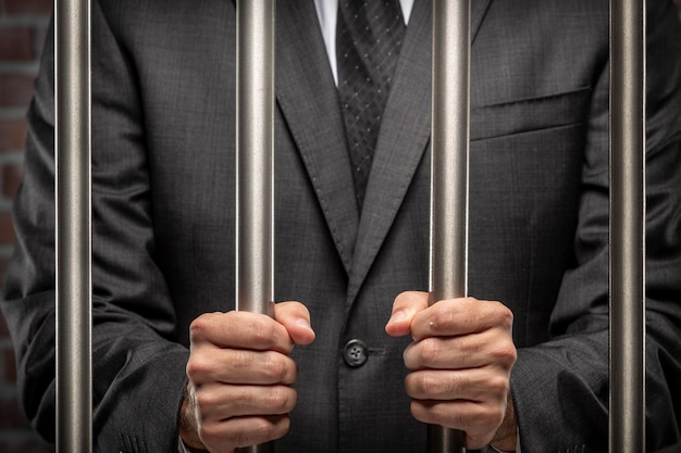 刑務所でバーを保持しているビジネスの男性。腐敗、腐敗した政治家、違法ビジネスの概念。レンガの背景。