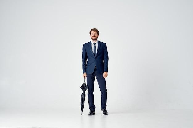 傘を持っているビジネスマンエレガントなスタイルの自信の天気