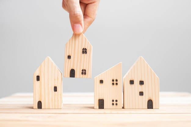 테이블 배경에 목조 주택 모델을 들고 사업가입니다. 가정, 위기, 경기 침체, 노숙자, 부동산, 구매 또는 임대 및 부동산 개념