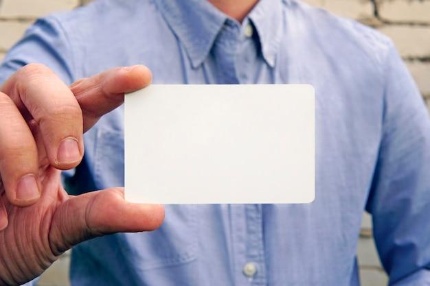 手に通りのレンガの壁に青いシャツを着たビジネスマンは、丸みを帯びた角でモックアップの空白の白いクレジット名刺ディスプレイを表示します。ビジネスブランディングのコンセプト。