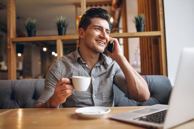 電話で話してコーヒーを飲むカフェのビジネスマン