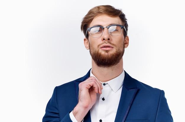 ジャケットとシャツを着たビジネスマンは、彼の顔の襟のモデルで眼鏡をまっすぐにします