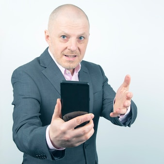 Деловой человек в куртке с мобильным телефоном в руке на свет