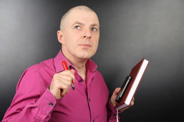Деловой человек в розовой рубашке с ручкой, телефоном и блокнотом в руке