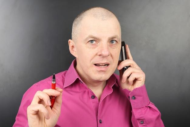 휴대 전화에 손에 펜으로 핑크 셔츠에 비즈니스 남자