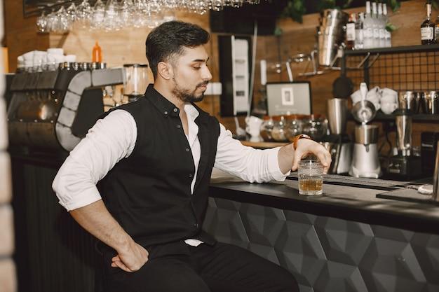 Деловой человек в пабе, пьет алкоголь